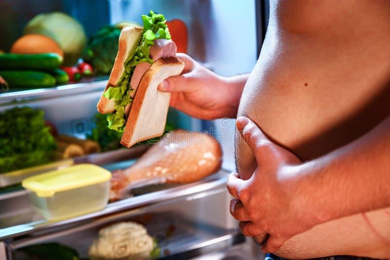 Hungrig man som rymmer en smörgås i hans händer och anseende bredvid arkivbild