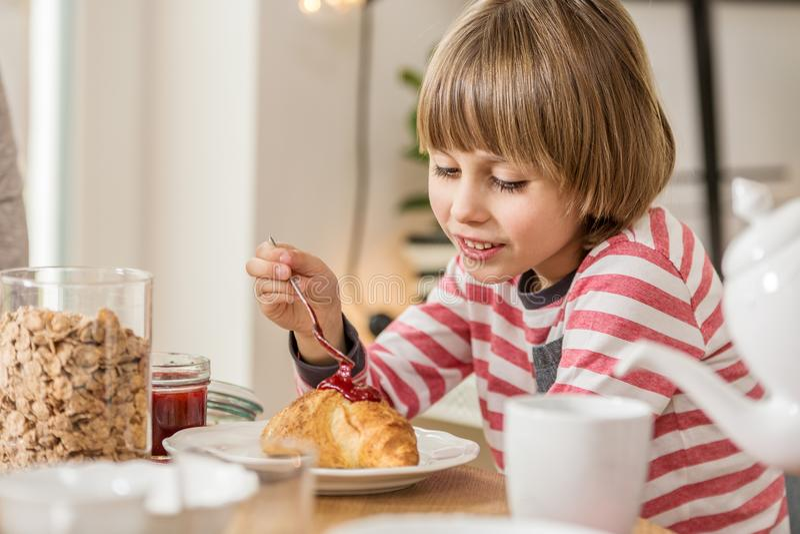 Hungrig pojke som äter frukosten royaltyfria bilder