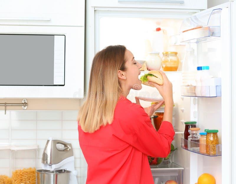 Hungrig ung kvinna som äter smörgåsen nära det öppna kylskåpet i kök royaltyfri bild