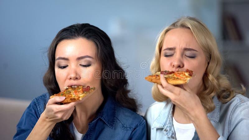 Hungriga kvinnliga v?nner som tycker om l?cker pizza, italiensk kokkonst, matleverans arkivbild