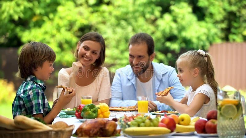 Hungriga ungar som äter läcker pizza, barns favorit- mat, italiensk kokkonst royaltyfri bild