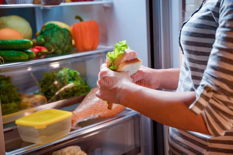 Hungrige Frau, die ein Sandwich in seinen Händen und in Stellung folgendes t hält lizenzfreie stockbilder