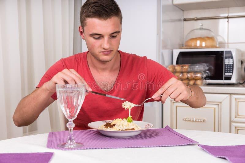 Hungrige junge Fleisch fressende gekochte Spaghetti-Hauptmahlzeit lizenzfreies stockbild