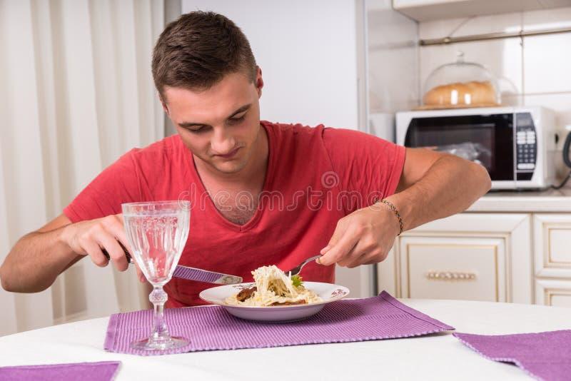Hungrige junge Fleisch fressende Teigwaren an Speisetische stockbilder