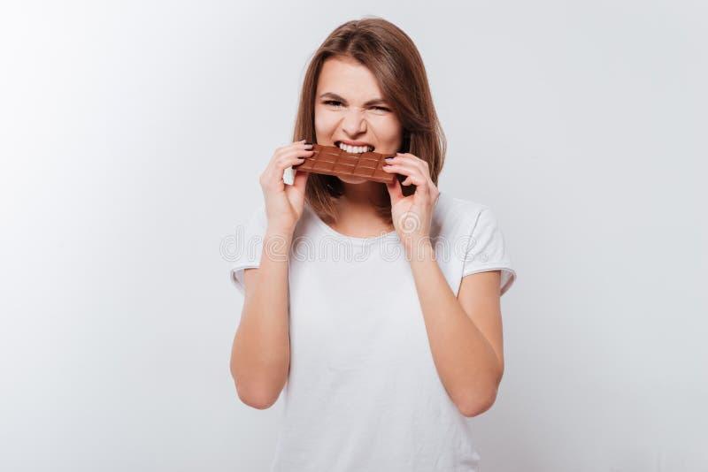 Hungrige junge Frau, die Schokolade isst stockfotos