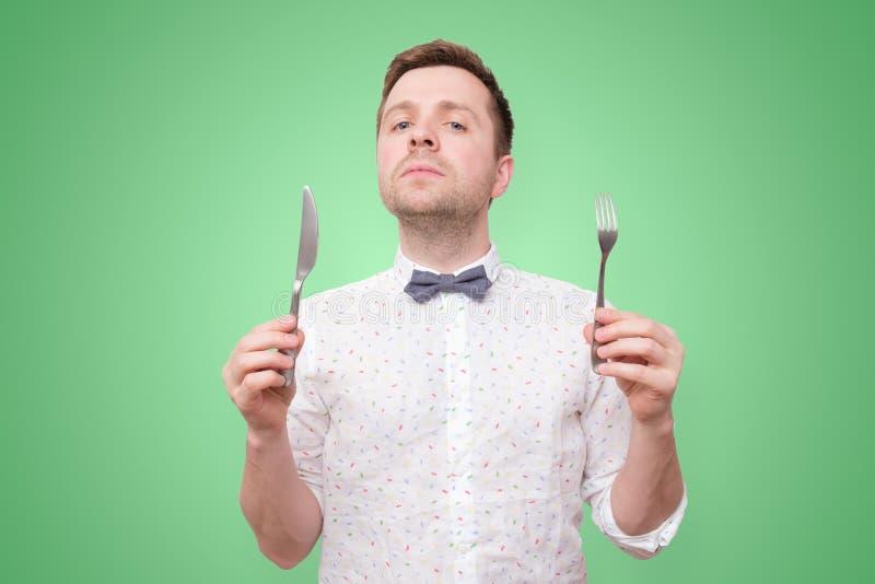 Hungrige Mannholdinggabel und -messer an Hand zu essen lizenzfreies stockbild