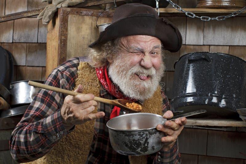 Hungriger alter Cowboy, der Bohnen von einer Kasserolle isst lizenzfreie stockbilder