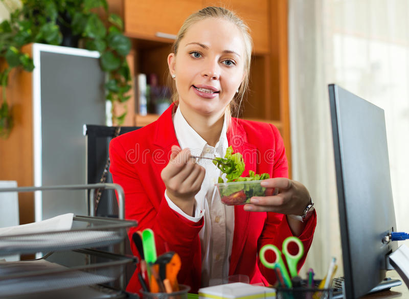 Hungriger Angestellter, der geschmackvollen Salat isst stockfoto