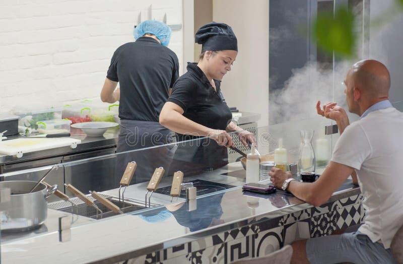 Hungriger Besucher, der nahe offener Küche mit dem Chef kocht italienisches Lebensmittel im modernen Restaurant isst lizenzfreies stockbild