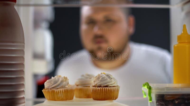 Hungriger dicker Mann, der Sahnekuchen im Kühlschrank nachts, Diabetesrisiko, Zucker betrachtet stockfotos