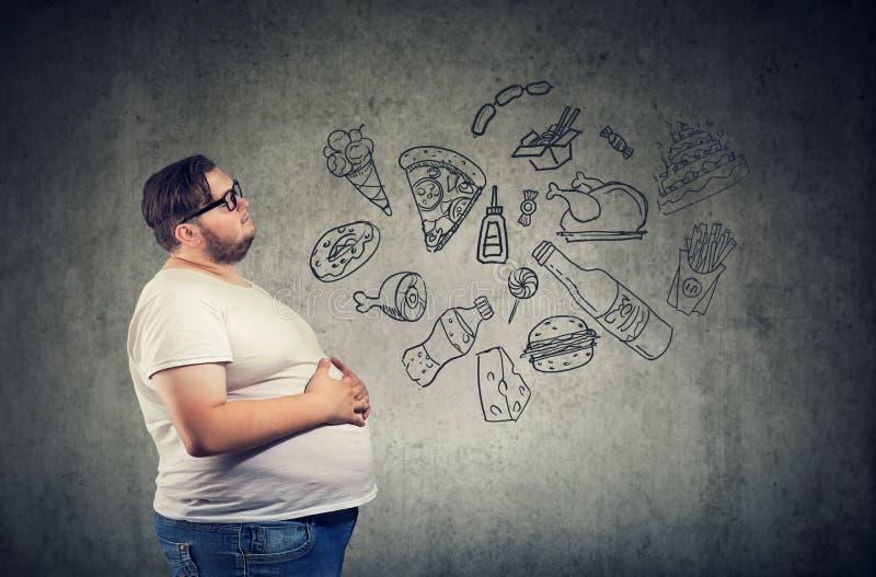 Hungriger dicker Mann, der an ungesunde Fertigkost denkt stockbilder