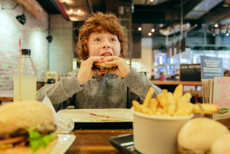Hungriger Junge isst Burger im Restaurant lizenzfreie stockfotografie