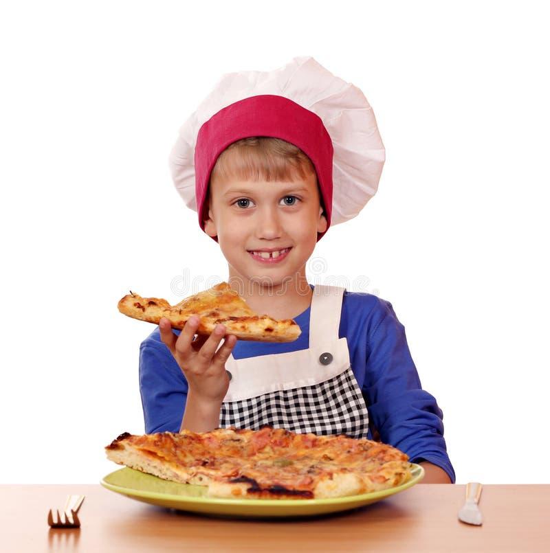 Hungriger Jungenchef essen Pizza lizenzfreie stockbilder