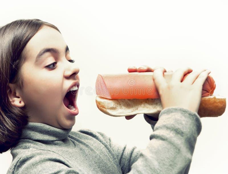 Hungriges Mädchen mit offenem Mund und mit riesigem Brot- und Wurstsandwich stockfotos