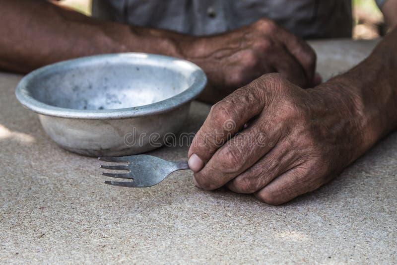 hungrigt Fattig gammal man& x27; s räcker en tom bunke Selektivt fokusera Armod i avg?ng _ fotografering för bildbyråer