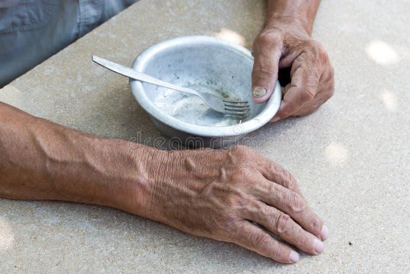 hungrigt Fattig gammal man& x27; s räcker en tom bunke Selektivt fokusera Armod i avg?ng _ royaltyfria foton