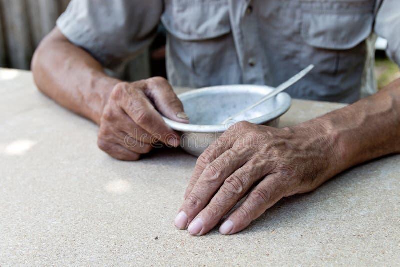 hungrigt Fattig gammal man& x27; s räcker en tom bunke Selektivt fokusera Armod i avg?ng _ arkivbilder