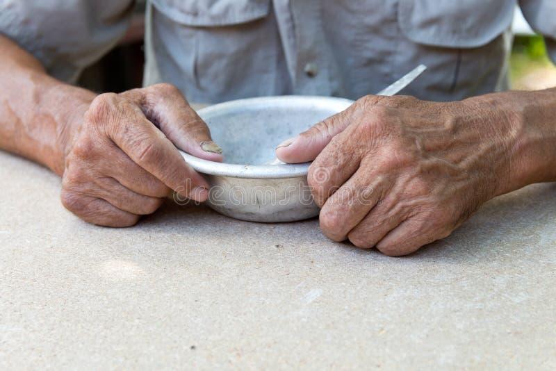 hungrigt Fattig gammal man& x27; s räcker en tom bunke Selektivt fokusera Armod i avg?ng _ royaltyfri foto
