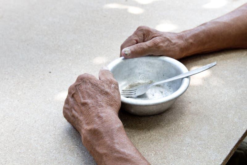 hungrigt Fattig gammal man& x27; s räcker en tom bunke Selektivt fokusera Armod i avg?ng _ royaltyfri fotografi
