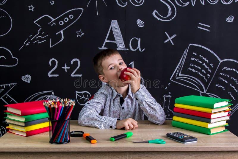 Hungrigt skolpojkesammanträde på skrivbordet med böcker, skolatillförsel som biter det röda äppleinnehavet i hans hand arkivbild