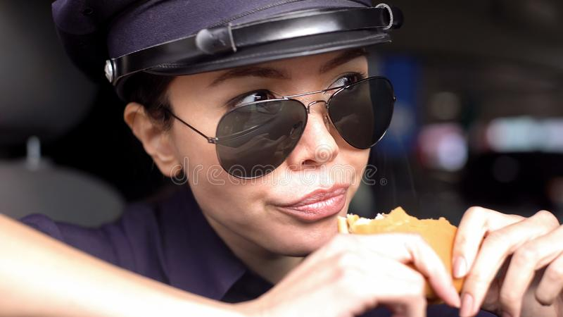 Hungry asian patrolwoman holding burger sitting in police car, greasy food-to-go. Stock photo royalty free stock images
