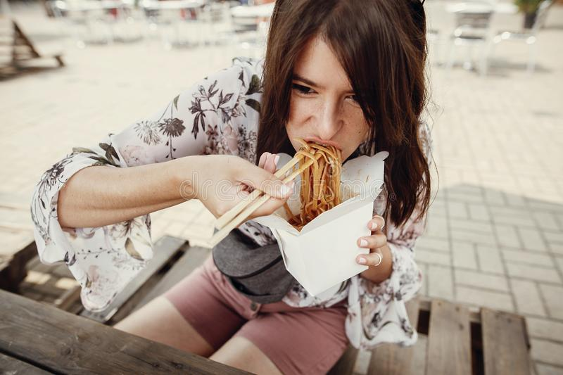 Hungry boho woman eating noodles in takeaway paper box. Food delivery. Asian Street food festival. Stylish hipster girl eating wok royalty free stock photo