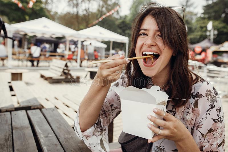 Hungry boho woman eating noodles in takeaway paper box. Food delivery. Asian Street food festival. Stylish hipster girl eating wok stock photos