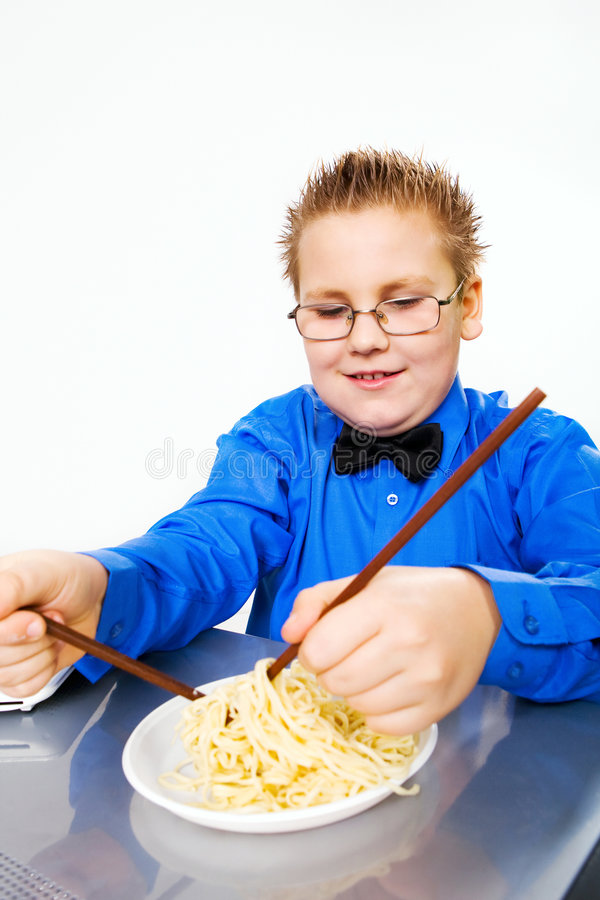 Hungry boy eating chinese noodles with sticks stock photos