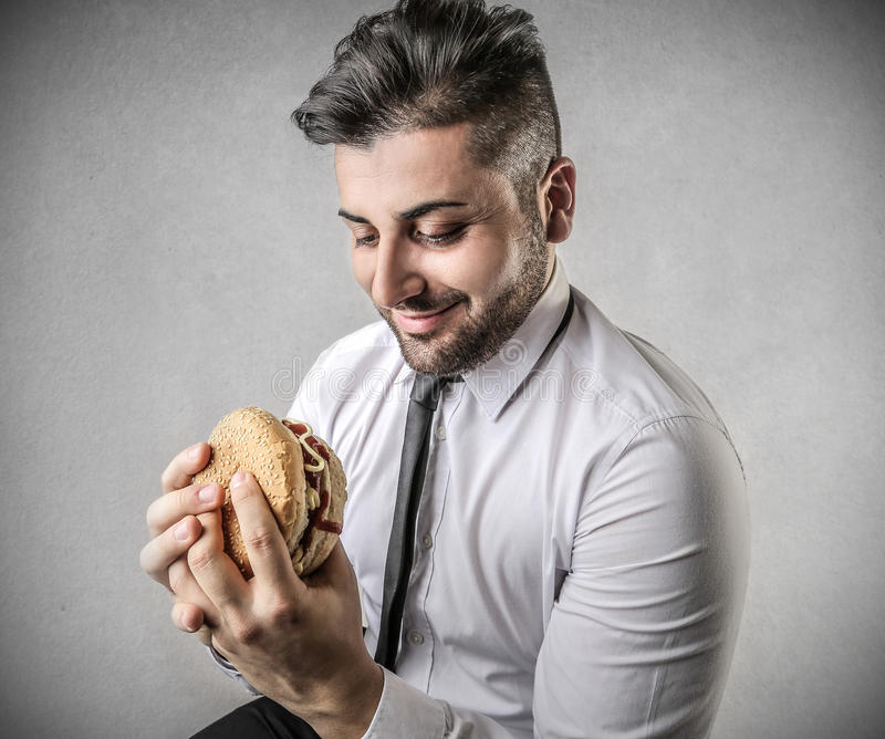 Hungry businessman during lunch break stock photos