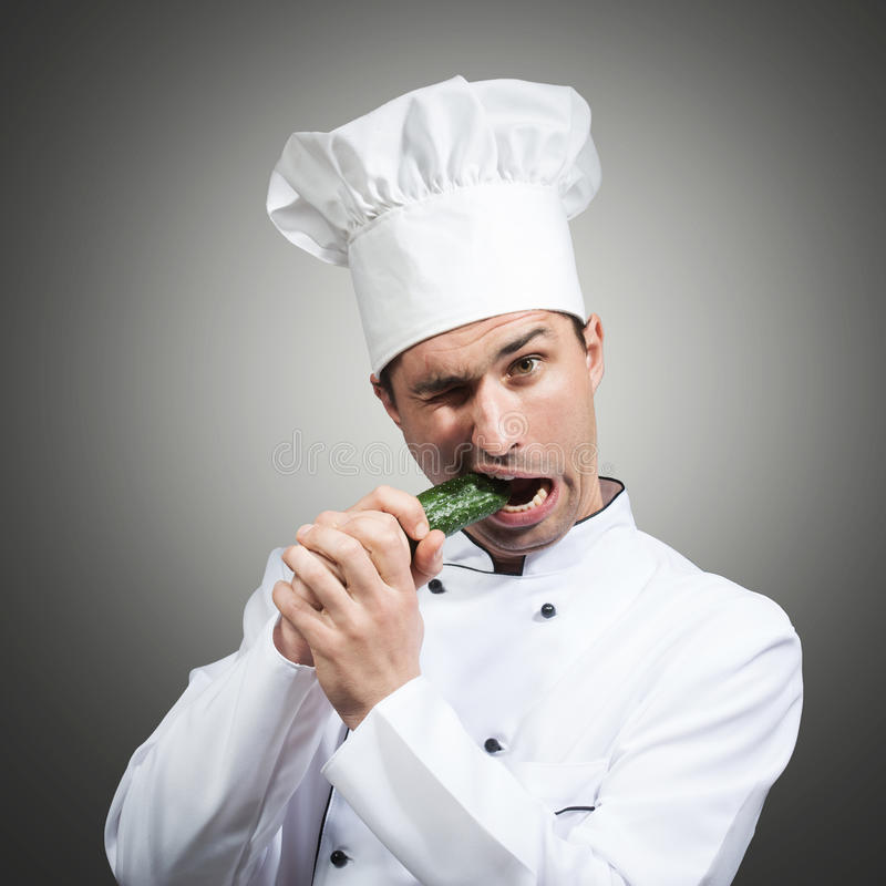 Hungry chef. Humorous portrait of a man in chef's hat nibbling on a cucumber, gray background stock photos