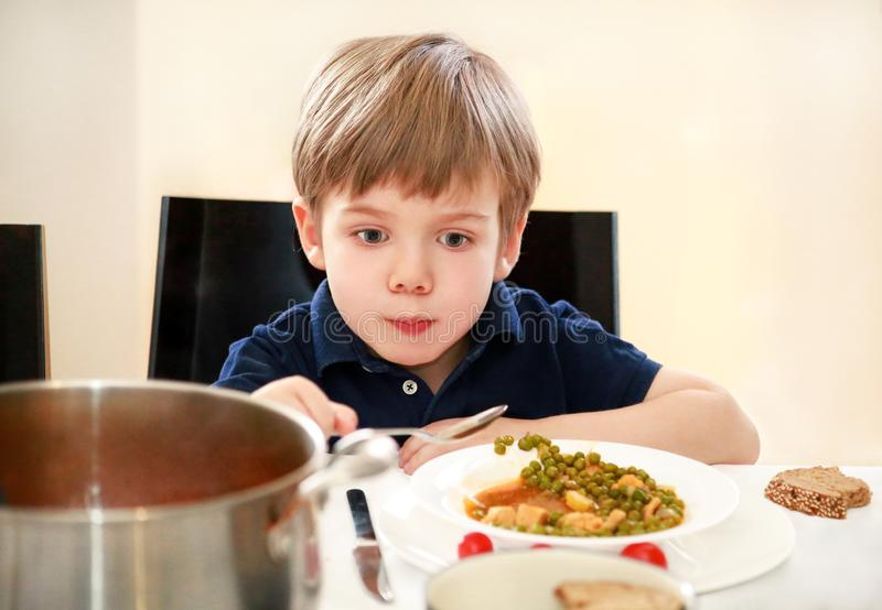 Hungry child sitting in chair at table in kitchen and eating with spoon of cooked peas with tomato. Kids meal and healthy food. stock image