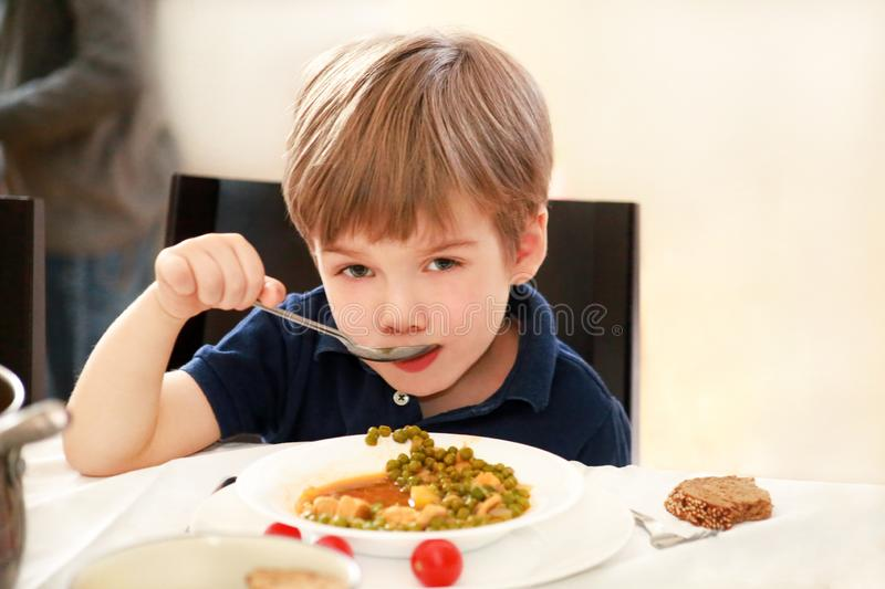 Hungry child sitting in chair at table in kitchen and eating with spoon of cooked peas with tomato. Kids meal and healthy food. royalty free stock image