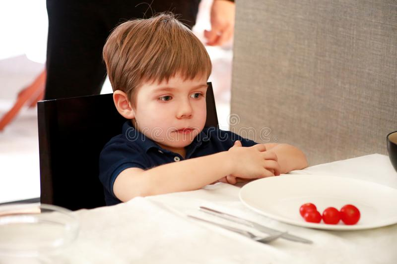 Hungry child sitting in chair at table in kitchen and waiting for meal and lunch. Boy is curious what he will get for meal. royalty free stock photography