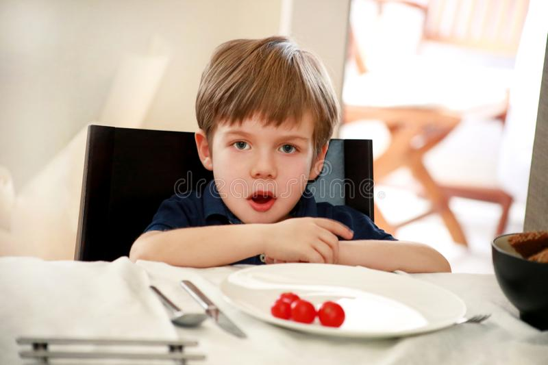 Hungry child sitting in chair at table in kitchen and waiting for meal and lunch. Boy is curious what he will get for meal. stock image
