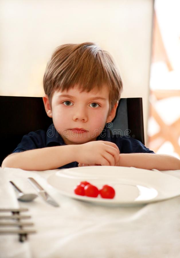 Hungry child sitting in chair at table in kitchen and waiting for meal and lunch. Boy is curious what he will get for meal. royalty free stock photos