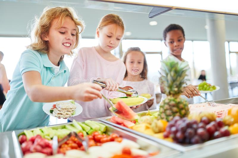 Hungry children get fruit at the buffet. Hungry children as students pick up fruit at the cafeteria`s buffet stock photo