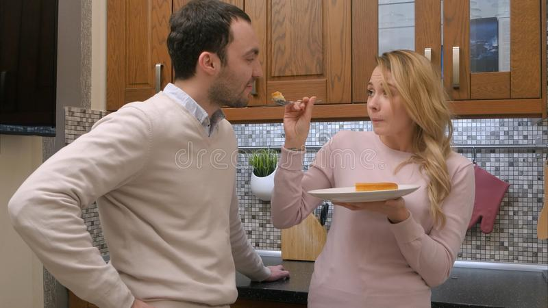 Hungry couple eating delicious cake, woman feeding man, in the kitchen at home royalty free stock photo