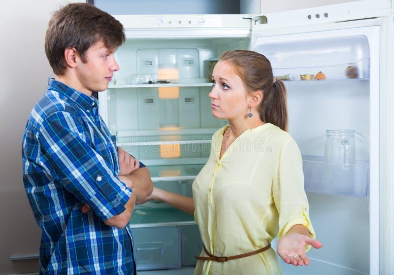 Hungry couple near empty fridge royalty free stock photos