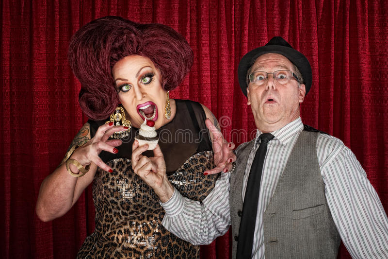 Hungry Drag Queen. And friend holding cupcake royalty free stock image