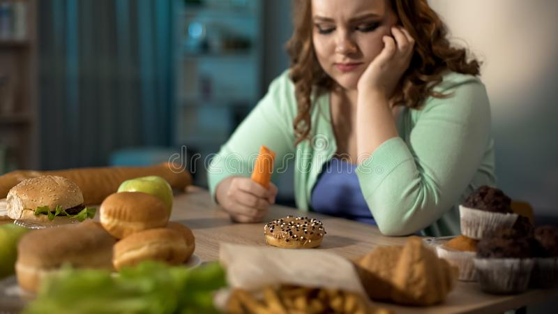Hungry fat lady eating carrot, dreaming about donut and fast food, healthy diet royalty free stock photo