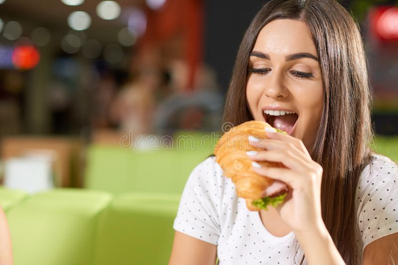 Hungry female biting croissant in cafe. Hungry female client sitting in cafe and biting delicious croissant with greens and ham. Beautiful brunette in white stock image