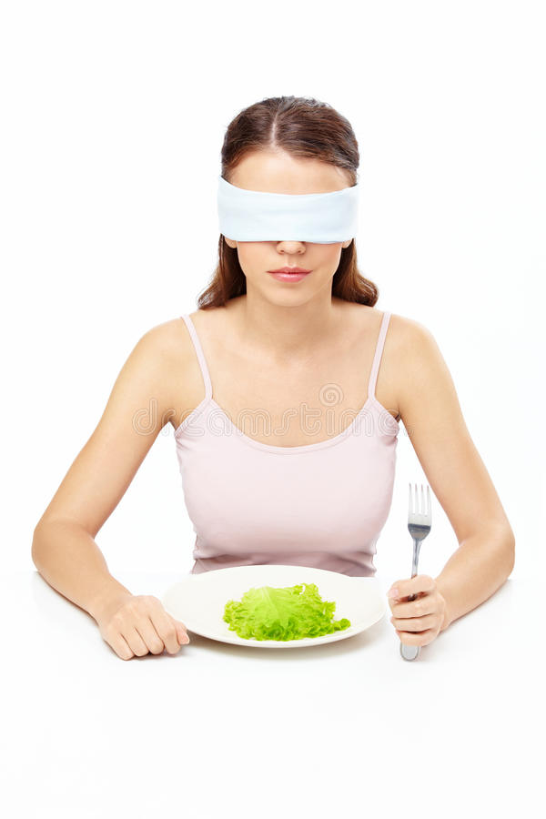 Hungry girl. Girl blindfold sits before plate with salad leaf, isolated royalty free stock images
