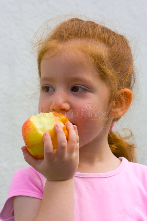 hungry girl with apple eating stock photography