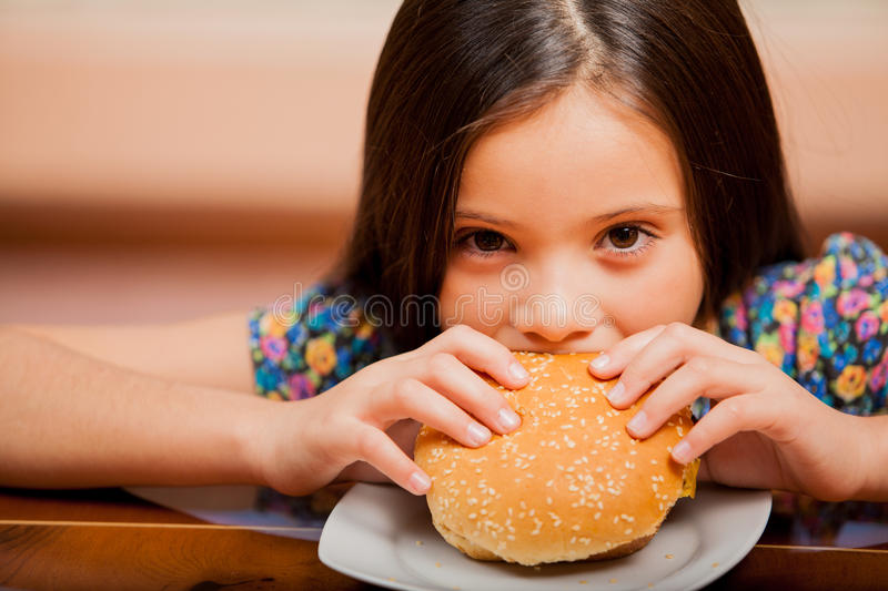 Hungry Girl Eating A Burger Stock Photography