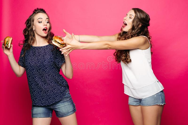 Hungry girl trying to get her friend`s burger. Food battle. Hungry girl with wavy hair trying to take her friend s burger pulling her arms towards it. Isolate stock images