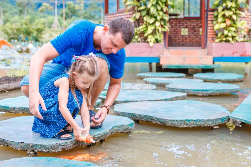 Hungry gold asian fish eats food from bottle in the pond. little beautiful girl with Dad feeds fish.  stock images