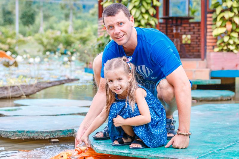 Hungry gold asian fish eats food from bottle in the pond. little beautiful girl with Dad feeds fish stock images