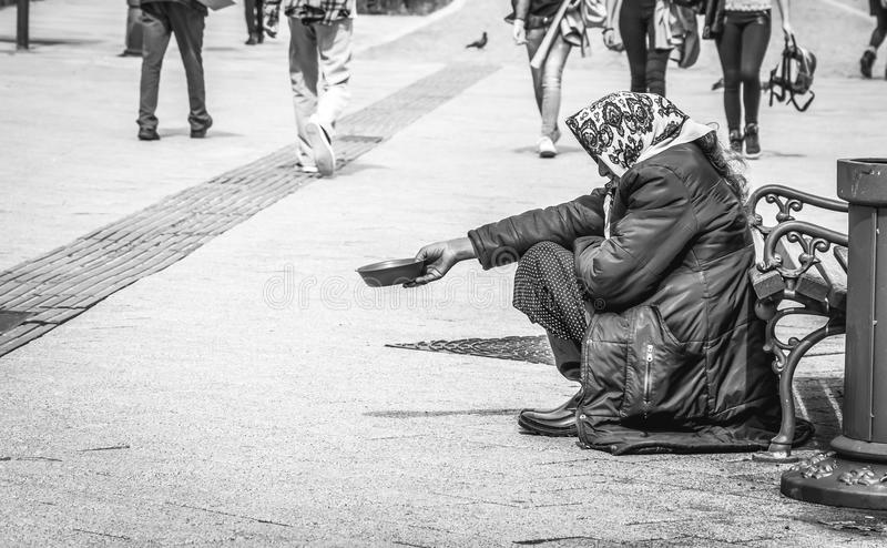 Hungry homeless beggar woman beg for money on the urban street in the city from people walking by, social documentary concept blac stock photography
