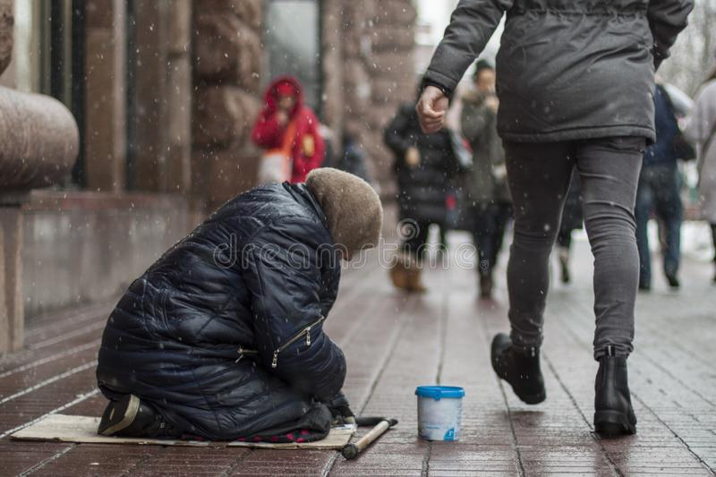 Hungry homeless beggar woman beg for money on the urban street in the city from people walking by, social documentary concept stock image
