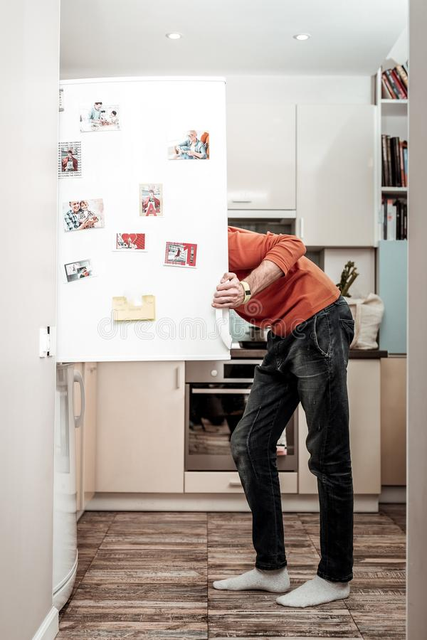 Hungry husband opening refrigerator after coming home from work royalty free stock photos